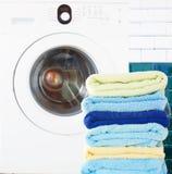 Куча чистых полотенец с стиральной машиной стоковая фотография