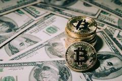 Куча штабелировать золотое bitcoin на 100 банкнотах доллара стоковая фотография