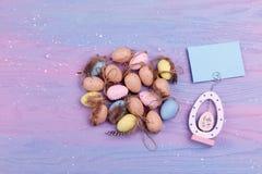 Куча яичек триперсток с пер на предпосылке лаванды деревянной с космосом экземпляра Концепция поздравительной открытки пасхи Стоковая Фотография RF