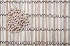 Куча chickpeas на striped предпосылке Стоковая Фотография RF