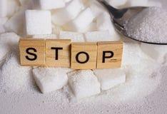 Куча h кубов белого сахара и остановить слово в печатных буквах как посоветуйте на злоупотреблении c калорий наркомании сверхнорм стоковые изображения
