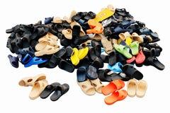 Кучи ботинок продали в рынке земли различных сочетаний цветов сельском, сандалиях, вскользь ботинках, старых На белой предпосылке стоковая фотография