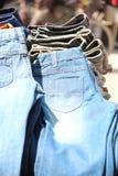 Кучи джинсыов на напольном блошинном Стоковое Фото