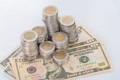 Кучи монеток и валюты доллара на белой предпосылке Стоковые Фото