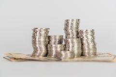Кучи монеток и валюты доллара на белой предпосылке Стоковые Фотографии RF