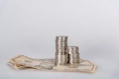 Кучи монеток и валюты доллара на белой предпосылке Стоковые Изображения