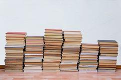 Кучи старых книг на поле в комнате с белыми стенами стоковое фото rf
