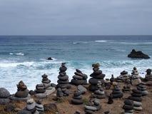 Кучи штабелированных каменных башен на пляже с волнами прибоя и голубым небом Стоковое Изображение RF