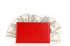 100 куч денег долларовых банкнот в красной тетради Стоковое Фото