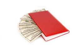 100 куч денег долларовых банкнот в красной тетради Стоковое Изображение