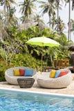 Кушетки бассейна и ротанга в тропическом саде, Таиланде Стоковая Фотография
