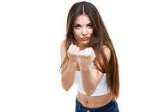 Кулаки красивой молодой женщины обхватывая стоя над белой предпосылкой Стоковое Изображение RF