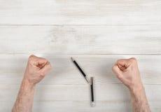 Кулаки крупного плана мужеские обхваченные на деревянной панели с сломленной ручкой Стоковое Изображение RF