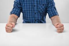 Кулаки крупного плана мужеские обхваченные на таблице Стоковые Изображения