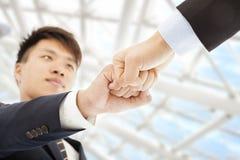 Кулак 2 бизнесменов вступает в противоречия один другого, который нужно отпраздновать Стоковая Фотография