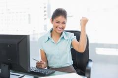 Кулак счастливой коммерсантки обхватывая на столе офиса Стоковое Изображение