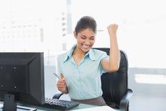 Кулак счастливой коммерсантки обхватывая на столе офиса Стоковая Фотография