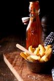 Кудрявый француз жарит с бутылкой кетчуп стоковые фотографии rf