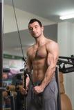 Культурист делая тяжелую тренировку для трицепса с кабелем Стоковые Фото