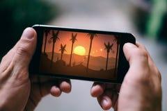 КЁЛЬН, ГЕРМАНИЯ - 27-ОЕ ФЕВРАЛЯ 2018: Крупный план мужских рук играя одиссею Alto's на Smartphone iPhone 5s стоковые фото