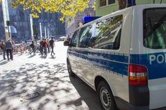 КЁЛЬН, ГЕРМАНИЯ, ОКТЯБРЬ 2018: Полицейская машина и люди идя в квадрат перед домом ` s Кёльна стоковая фотография