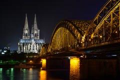 Кёльн ночой, горизонтом с церковью Dom и мостом Стоковые Изображения