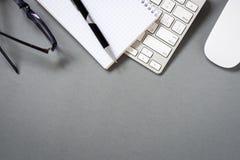 Клавиатура, мышь и канцелярские товары на сером столе Стоковая Фотография
