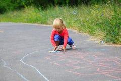 Классики чертежа маленькой девочки на спортивной площадке стоковые фото