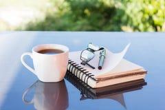 Классическая белая чашка черного кофе украшенная с примечанием и ручкой с зеленой предпосылкой природы Стоковые Изображения RF