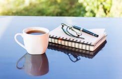 Классическая белая чашка черного кофе украшенная с примечанием и ручкой с зеленой предпосылкой природы Стоковое фото RF
