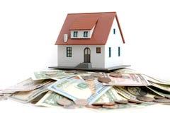 Классическая домашняя модель с кучей монеток и банкнот изолированных на белой предпосылке Стоковое Фото