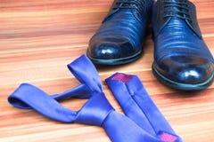Классические ботинки людей и голубая связь на деревянной предпосылке Стоковое Изображение