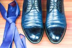Классические ботинки людей и голубая связь на деревянной предпосылке Стоковое Изображение RF