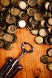 Классические консервооткрыватель бутылки и куча крышек пивной бутылки Стоковая Фотография RF