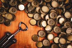Классические консервооткрыватель бутылки и куча крышек пивной бутылки Стоковое Фото