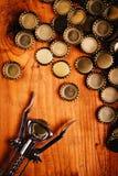 Классические консервооткрыватель бутылки и куча крышек пивной бутылки Стоковые Изображения