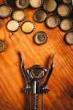 Классические консервооткрыватель бутылки и куча крышек пивной бутылки Стоковые Фотографии RF