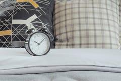 Классические часы и подушки стиля на белых постельных принадлежностях Стоковое фото RF
