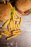 Классические cheeseburgers на деревянной плите Стоковые Фото