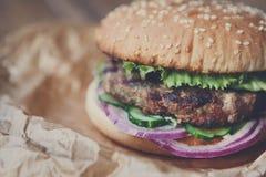 Классический американский бургер, фаст-фуд на деревянной предпосылке Стоковое Изображение