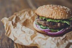 Классический американский бургер, фаст-фуд на деревянной предпосылке Стоковая Фотография