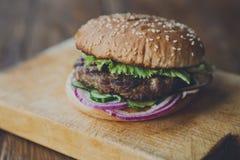 Классический американский бургер, фаст-фуд на деревянной предпосылке Стоковые Фото