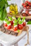 Классический салат канапе Caprese итальянки с томатами, моццареллой и свежим базиликом Стоковое Изображение