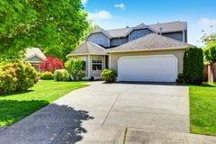 Классический экстерьер дома рассказа американца 2 с гаражом, подъездной дорогой и хорошо, который держат садом Стоковые Фотографии RF