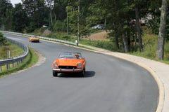 2 классических оранжевых итальянских автомобиля спорт на дороге Стоковые Фотографии RF