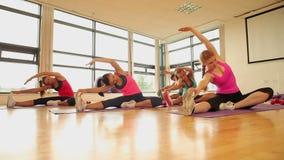 Класс и инструктор фитнеса протягивая ноги сток-видео