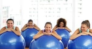 Класс фитнеса в склонности студии на шариках тренировки усмехаясь на камере видеоматериал