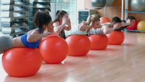 Класс фитнеса делая обратный сидит поднимает сток-видео