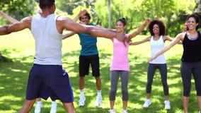 Класс фитнеса делая скача jacks в парке акции видеоматериалы