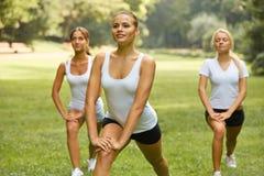 Класс фитнеса Красивые молодые женщины делая тренировку на PA лета Стоковая Фотография